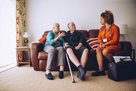 Caregiver and patient talking with support person on the sofa in their living room