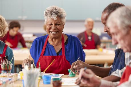 Older woman smiling during an arts and crafts class