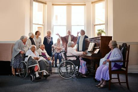 A choir of older women in front of windows, singing. Some are standing, some are seated in chairs or wheelchairs