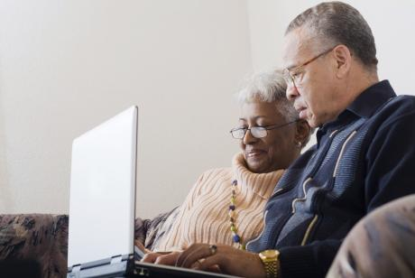 An older couple looking a computer together