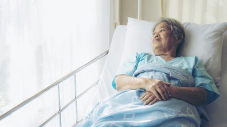 older woman alone in the hospital. She is lying in her hospital bed, looking out the window.