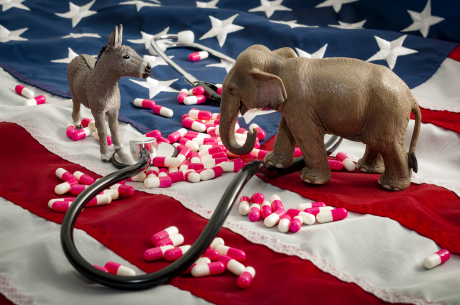 Donkey and elephant figurines face each other on a U.S. flag. A stethoscope and pills are scattered around them,
