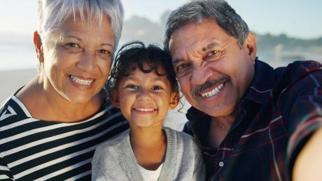 An older Latinx couple with their granddaughter. All three smiling at the camera