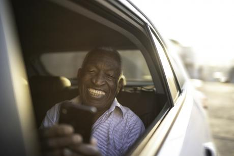 An older Black man in the back seat of a car with the window down smiling, looking at his phone
