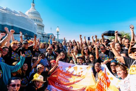 A large group of diverse people wearing National Domestic Workers Alliance shirts wave, hold banners, in front of the U.S. Capitol. Ai-jen Poo stands in the middle.