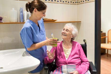 Care worker handing an older woman her toothbrush. Both are smiling.