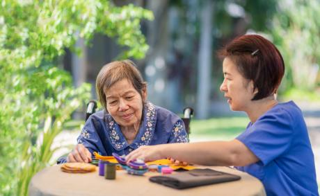 Older woman with caregiver doing crafts