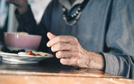closeup of an older man's hand next to his plate of food