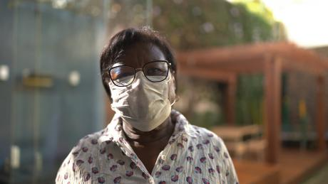 Portrait of a older Black woman using face mask