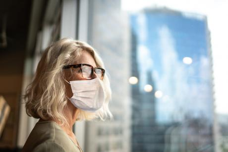 Mature professional woman looking out of window with face mask