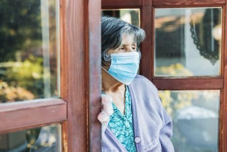an older woman stands in a doorway looking outside, she's wearing a mask