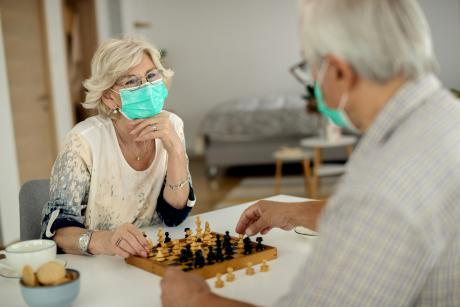 An older woman and man play chess, wearing masks