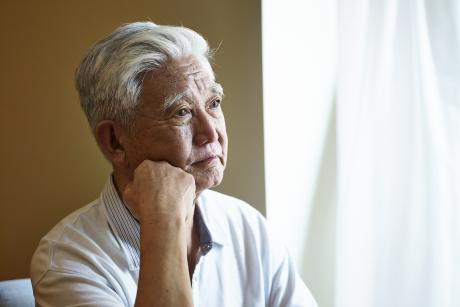 older man looks out window, seems sad or contemplative
