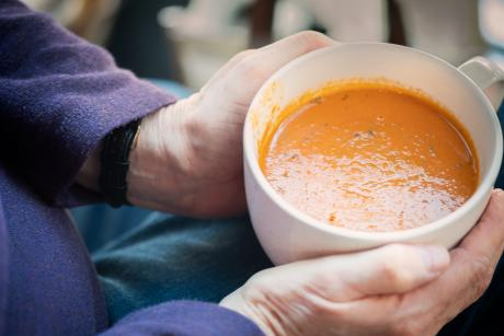 Images of an older adult's hands holding a bowl of soup