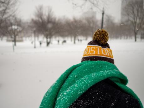 Person from behind wearing a Boston hat, Boston Common in Snow