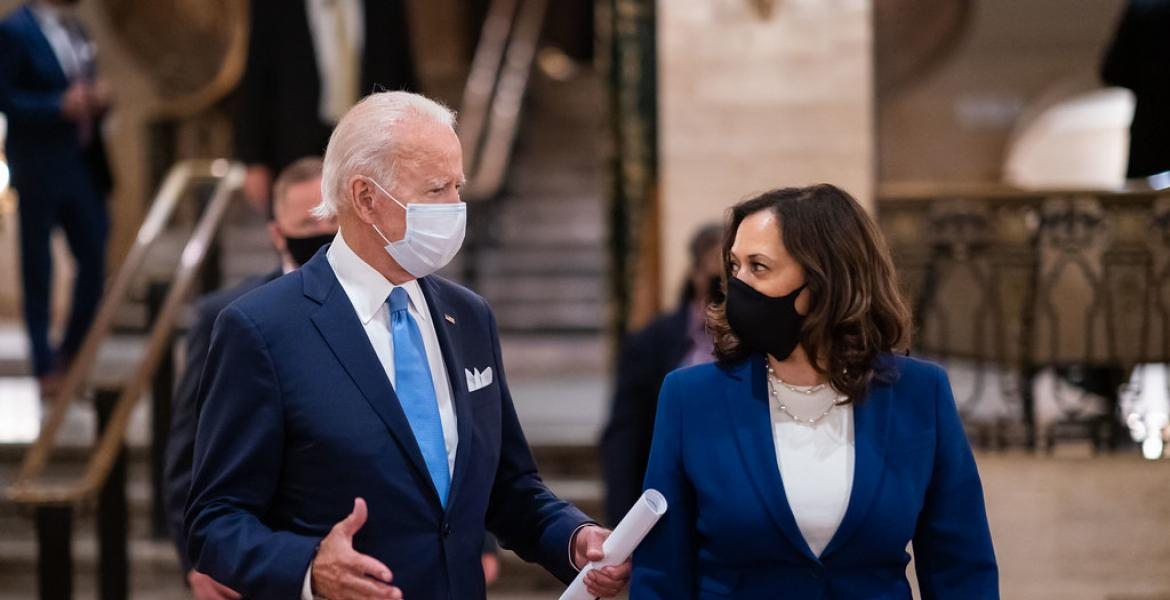 Joe Biden and Kamala Harris talking, both wearing masks